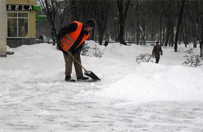 Работник коммунальной службы чистете снег возле Полтавской обласной библиотеки