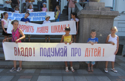 Дети держут плакаты против закрытия школы