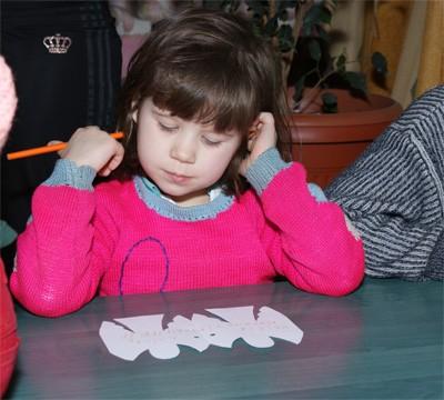 Діти пишуть на листочку у вигляді янгола, що хочуть отримати на Новий рік
