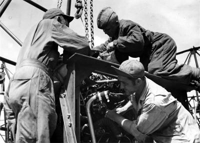 Сержант John M. Bassett, Леонид Бойков, сержант Michael Cajolda обслуживают двигатель американского тяжелого бомбардировщика Б-17 «Летающая крепость». 169-я авиабаза