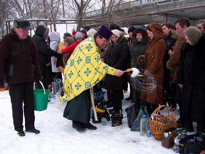 Отець Дарій окропив принесені людьми баночки з водою