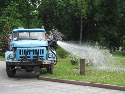 Водитель поливочной машины поливает газоны