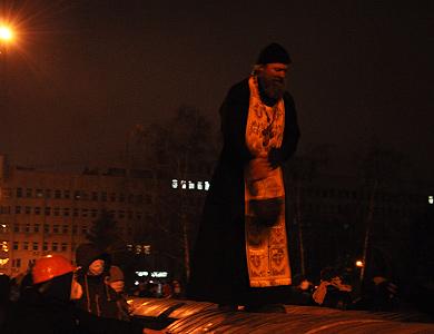 Священик виступає перед протестуючими