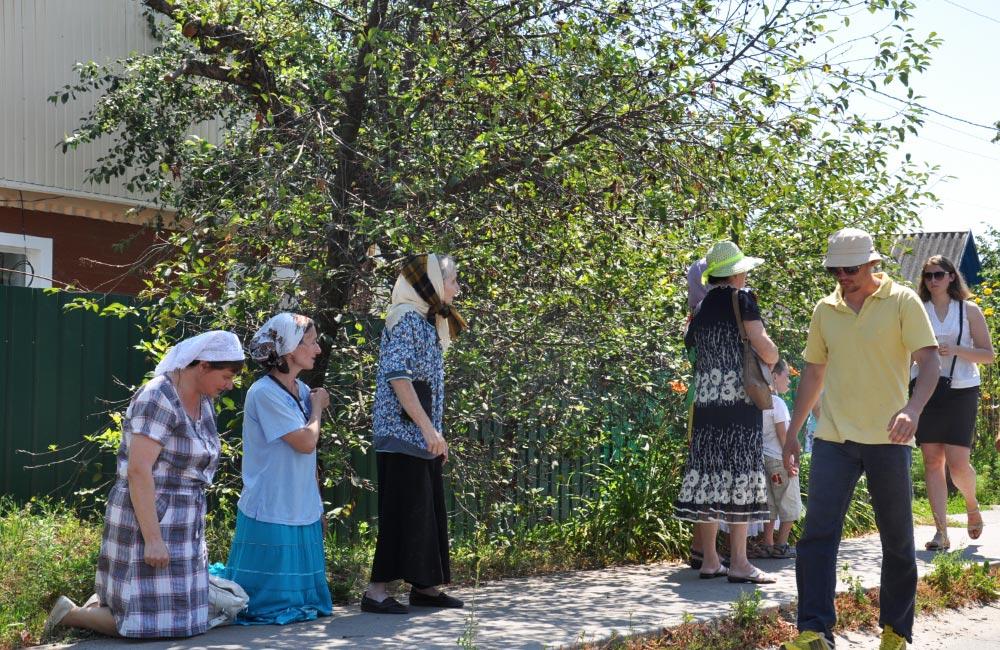 Місцеві жителі стають на коліна перед хресною ходою