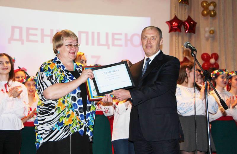 Міський голова Олександр Мамай вручає сертифікат на 100 тисяч гривень