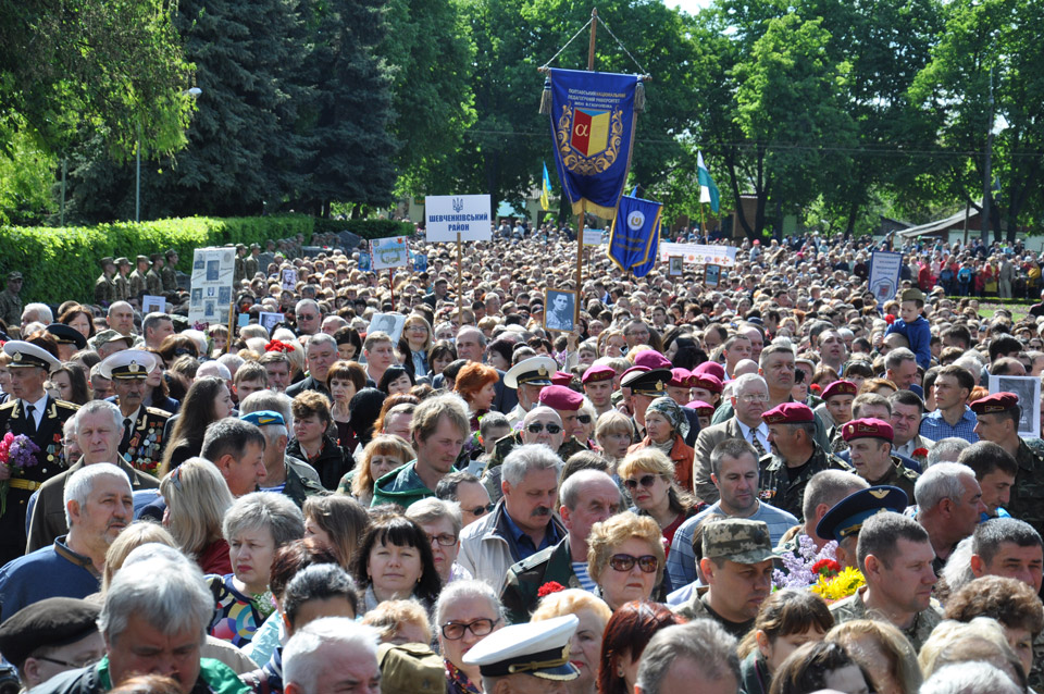 Люди стоять в черзі, щоб покласти квіти перед пам'ятником солдату.