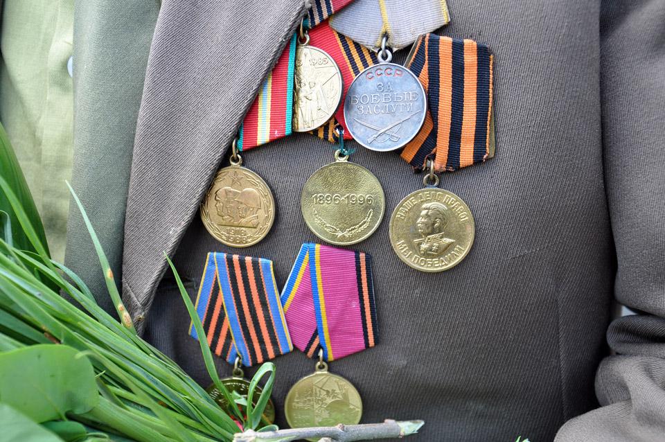 Багато присутніх були з медалями на грудях, але дійсно учасників бойових дій одиниці. У цього ветерана бачимо медаль за«Бойові заслуги», та медаль за«Перемогу» (оранжево-чорна стрічка). Ці відзнаки свідчать, що він дійсно брав участь у війні.