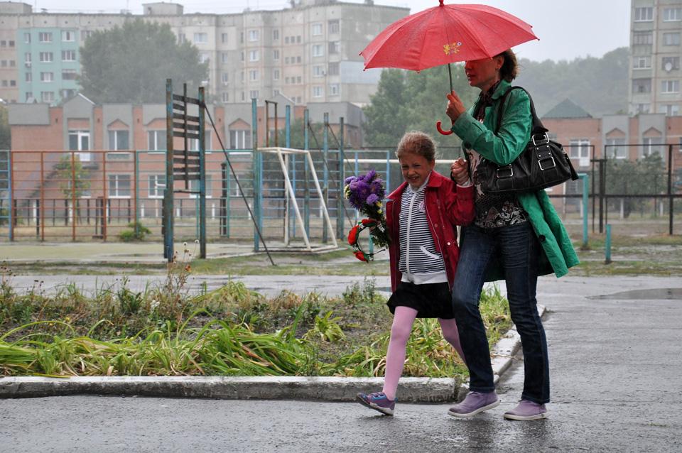 Донька із мамою поспішають на урочистості із традиційними квітами, прикриваючись парасолькою.