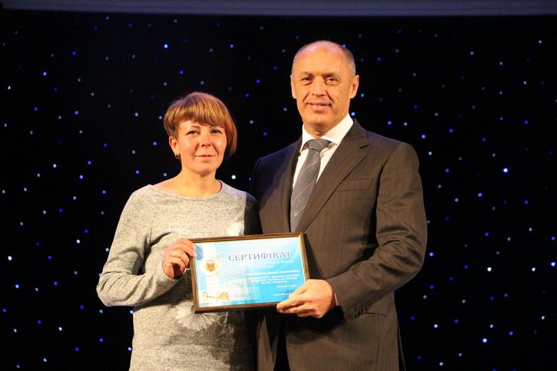Міський голова Олександр Мамай вручає сертифікат на житло Оксані Григоренко