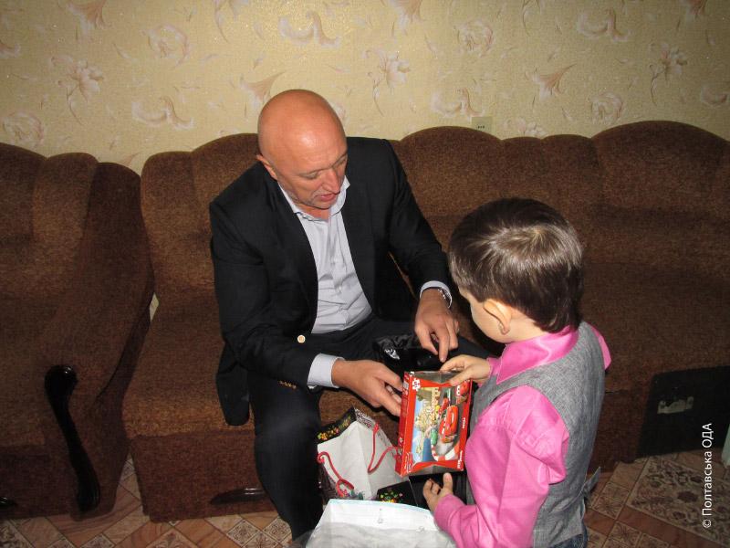 Валерій Головко допомагає маленькому Ярославу діставати подарунки