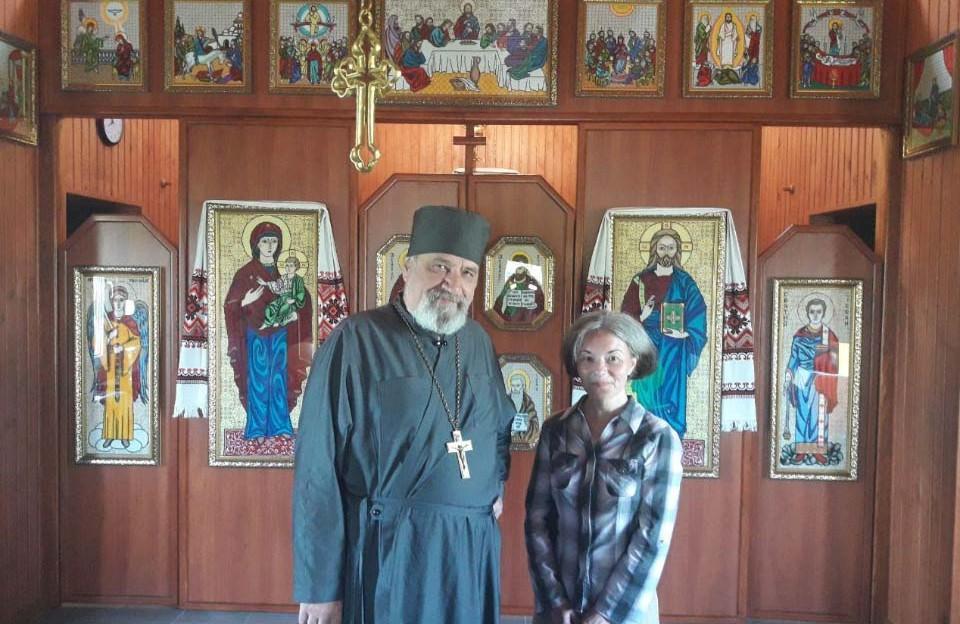 Отець Юрій Кролевський та парафіянка Галина Денис на фоні вишитого іконостасу