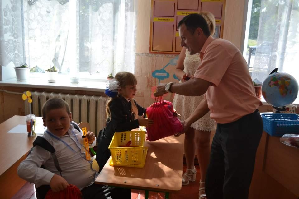 Євген Почечун вручає подарунки першокласникам Сонячного Старицьківської сільради
