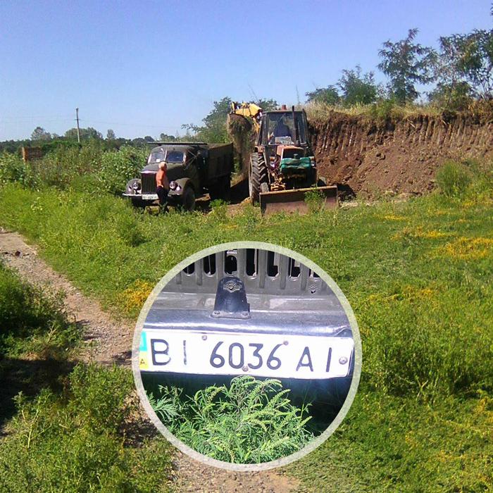 На території КП «Декоративні культури» трактор комунальників навантажує приватну вантажівку чорноземом