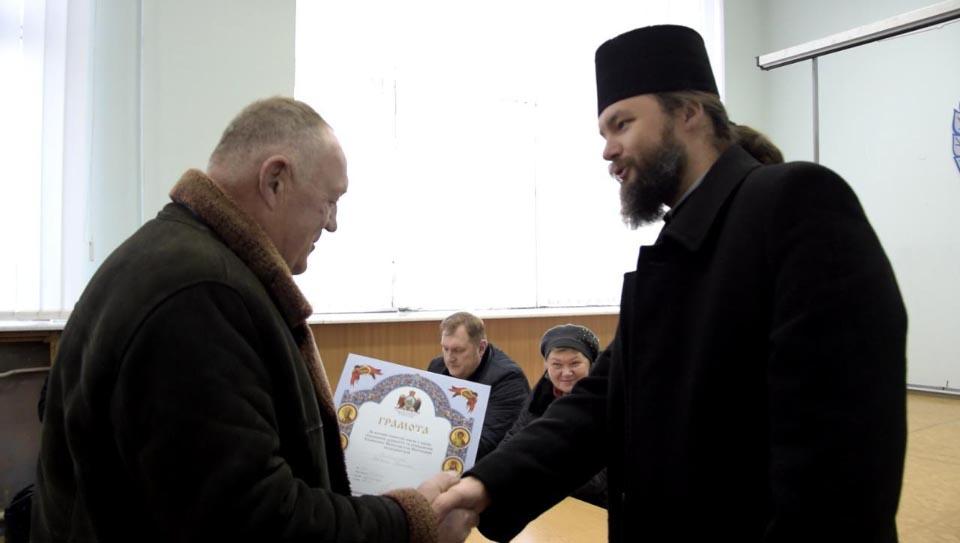 Архієпископ Полтавський і Кременчуцький Федір вручає почесну грамоту раднику з виробничих питань Полтававодоканалу Василю Забишному