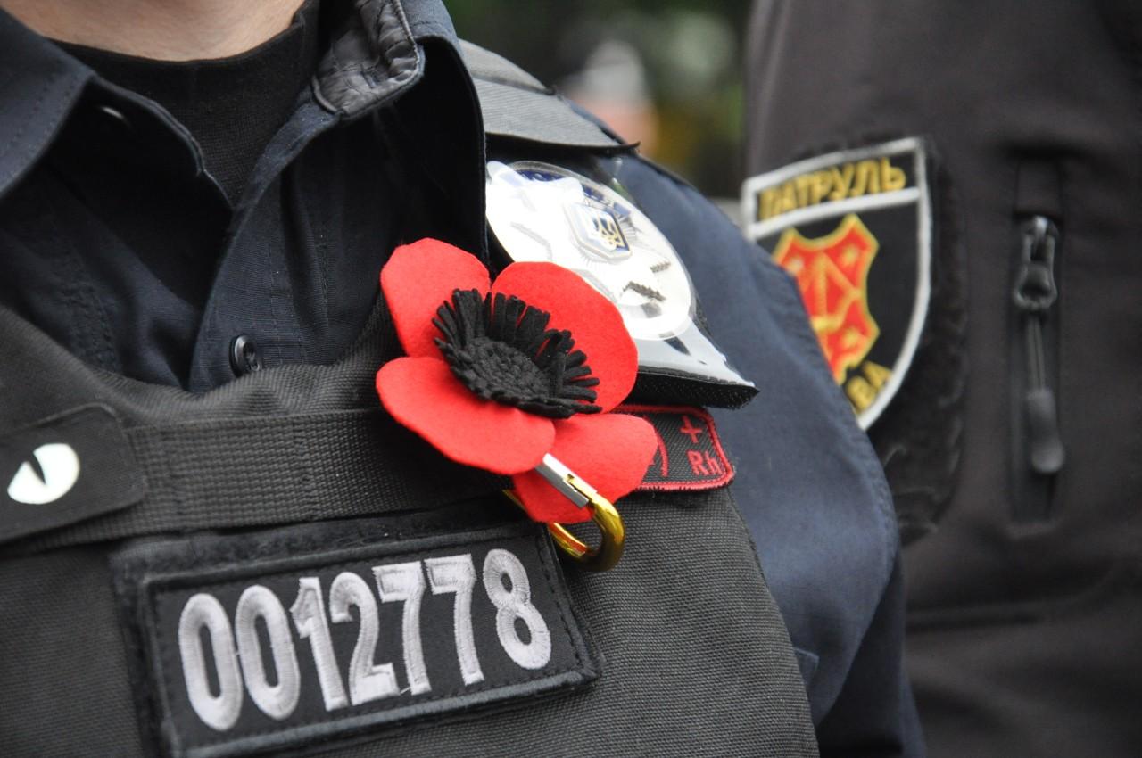 Поліцейський з червоною маківкою на грудях.