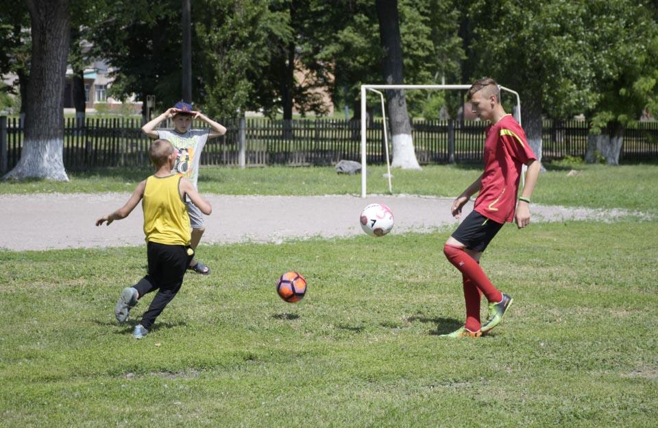 Члени футбольної команди грають новими м'ячами