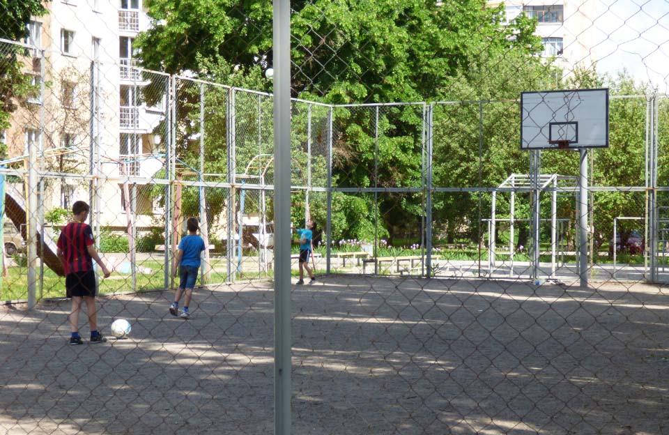 Діти грають на новому майданчику футбольним м'ячем, але цю гру навіть важко назвати футболом — бо відсутні ворота