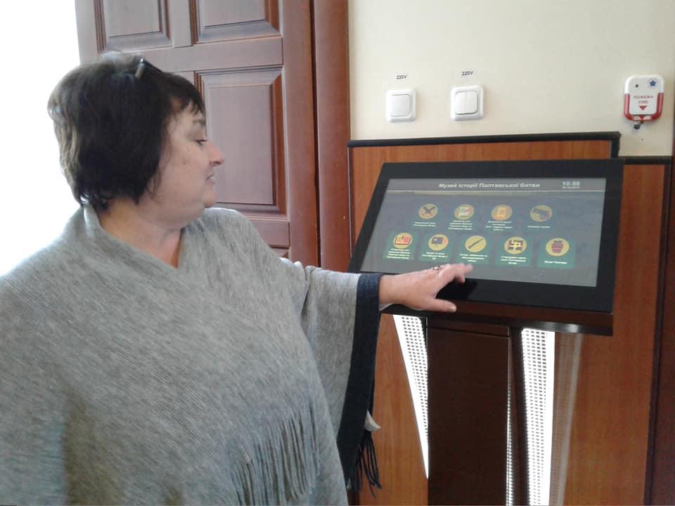 Директорка музею Наталія Білан показує відвідувачам новий електронний інформаційний термінал