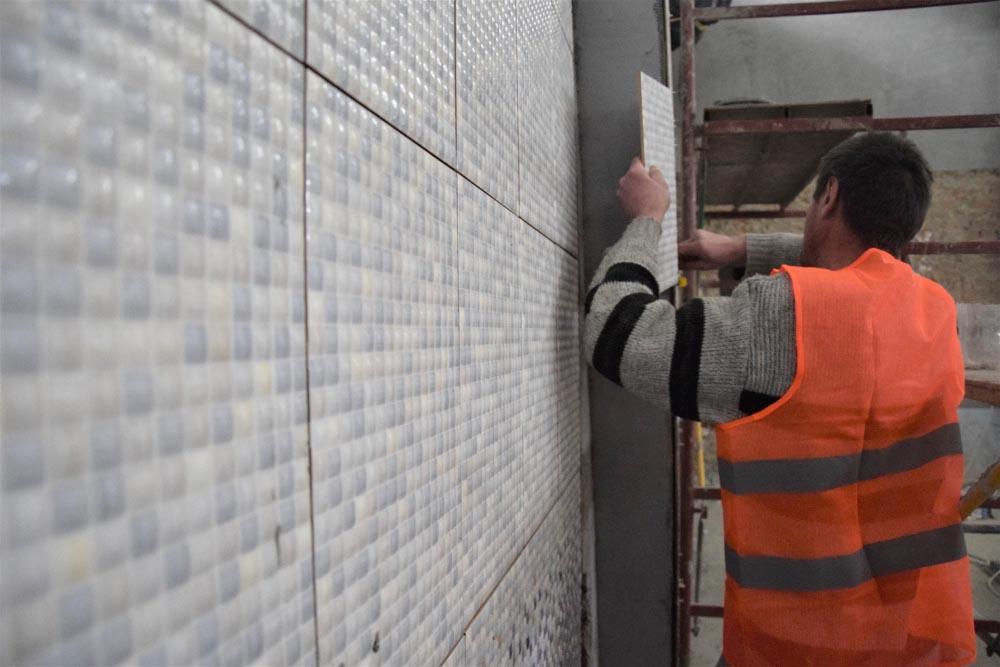 Фахівці проводять облицювання стін плиткою