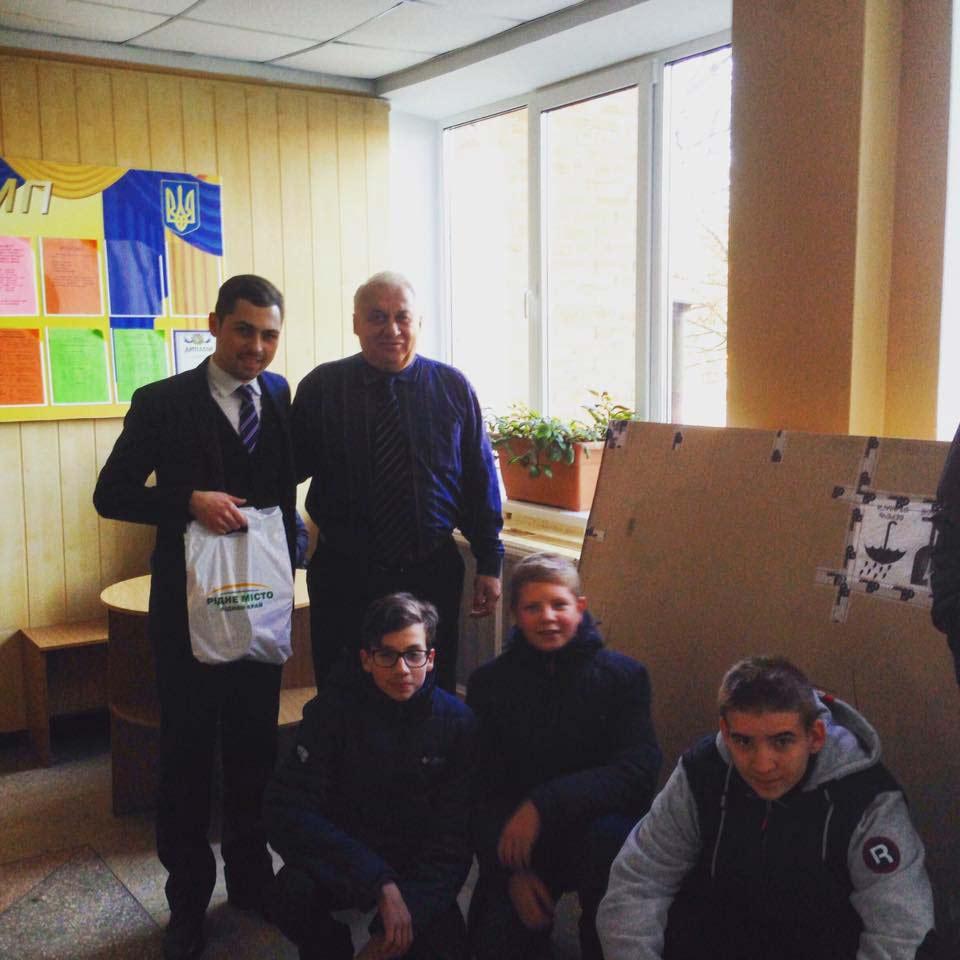 Е. Волков вручає подарунки з лого партії (джерело — сторінка партії «Рідне місто» у Facebook)