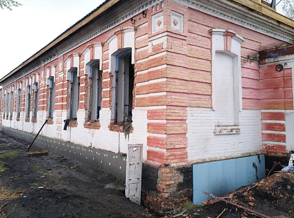 Фасад будівлі і чи то укріплення, чи то утеплення фундаменту