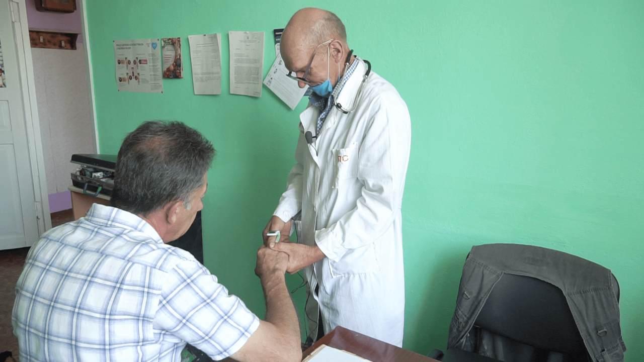 Петро Закотій перевіряє пульс пацієнта на новому пульсоксиметрі
