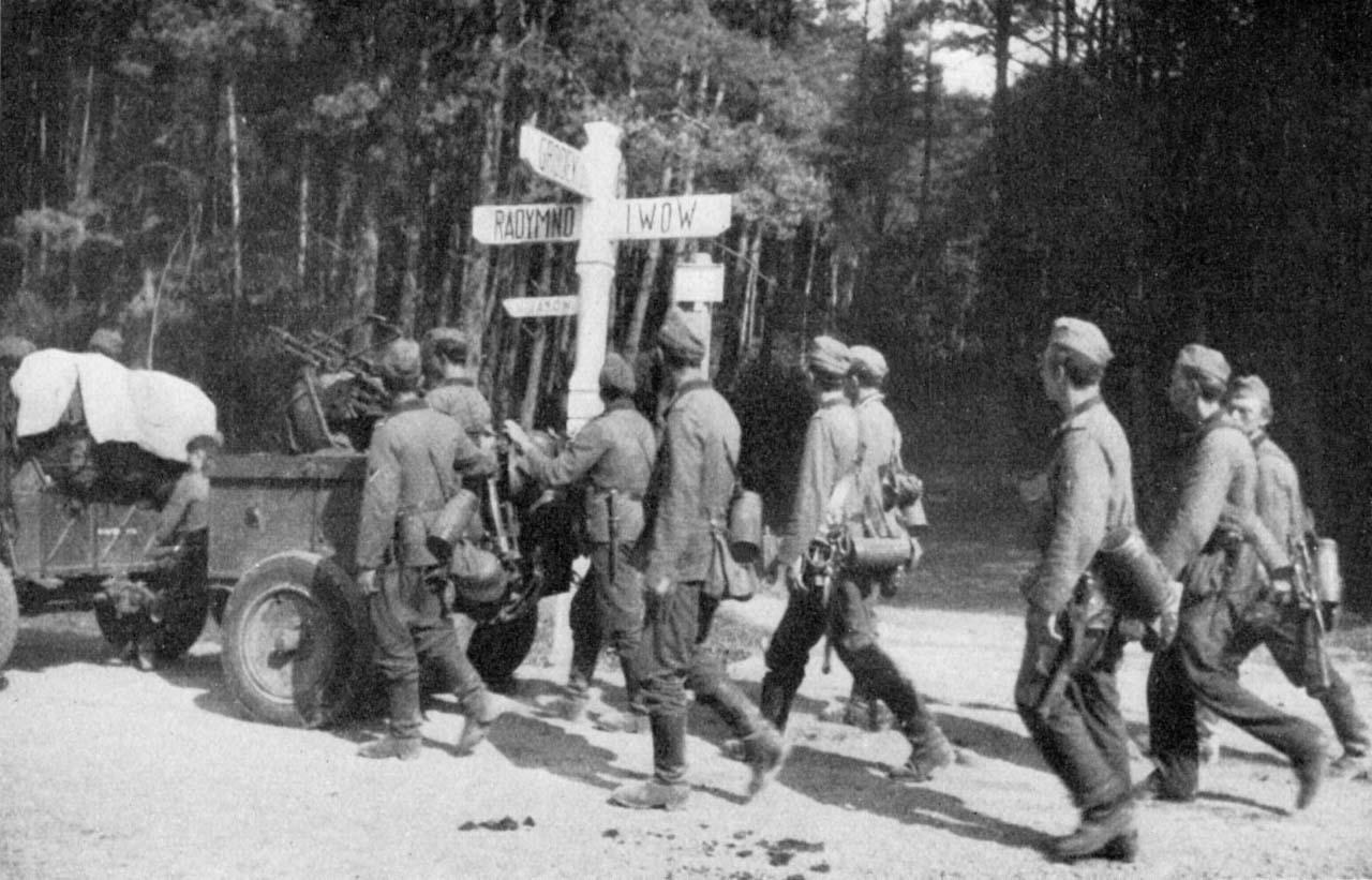 Німецькі солдати проходять біля дорожного знаку «На Львів»