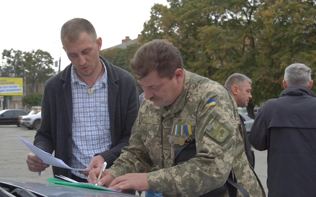 Віталій Турпітько підписує акт прийому-передачі відремонтованого автомобіля для військових
