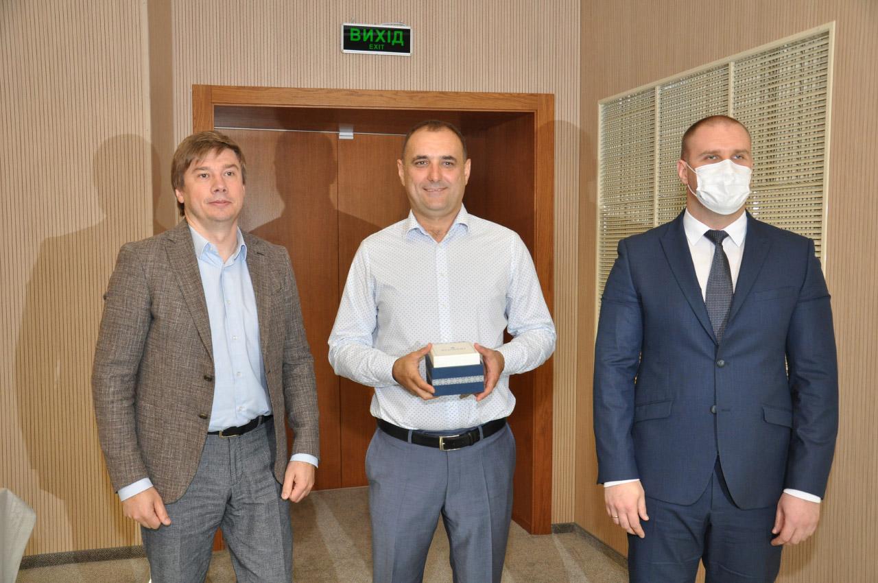 Олександр Біленький та Олег Синєгубов дарують Валерію Прядку годинник обласної ради